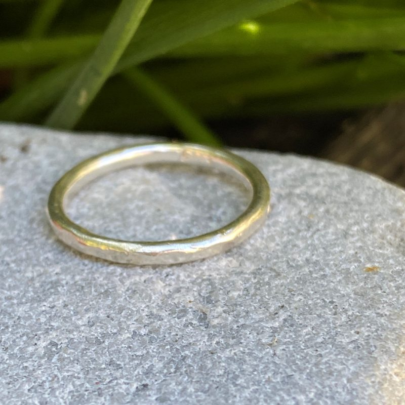 sterling silver stacking ring with a lightly hammered texture on a stone