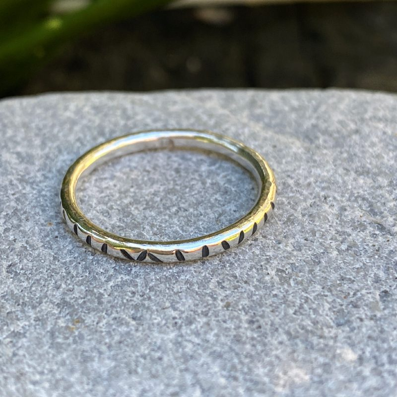 sterling silver stacking ring with linear texture on a stone