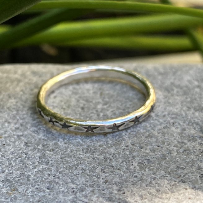 sterling silver stacking ring with star design on a stone