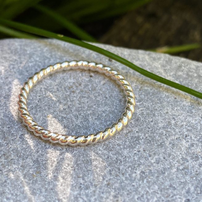 sterling silver stacking ring with a twisted design on a stone