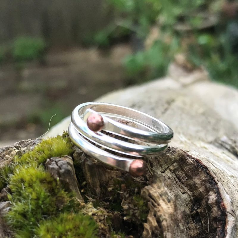 Sterling silver wraps twice with two copper bearings at the ends.