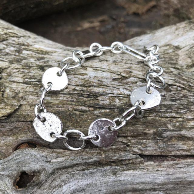 Handmade sterling silver link bracelet on bark background