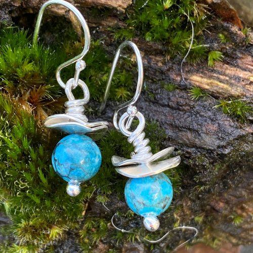 sterling silver and turquoise dangling earrings on a wood backdrop