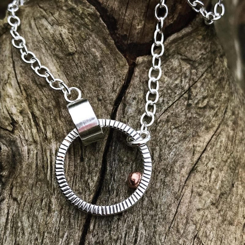 Sterling silver circle hanging asymmetrically from a sterling silver chain