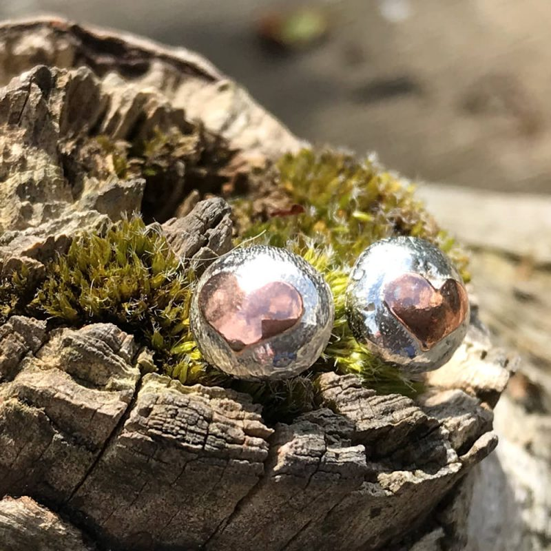 pair of sterling silver nuggest earrings adorned with a copper heart