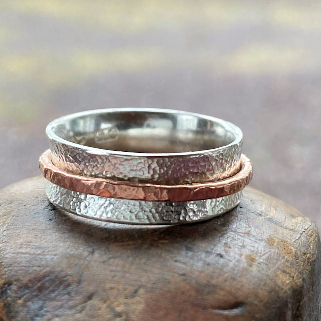 Side view of sterling silver spinner ring with single copper spinner