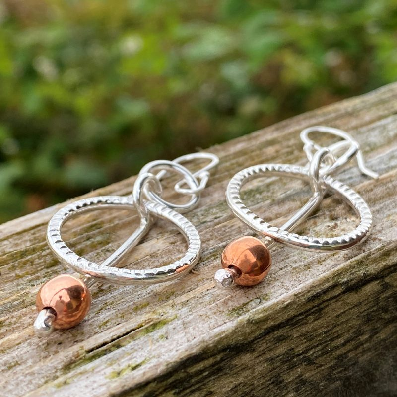 handcrafted sterling silver and copper circle earrings resting on a wooden fence
