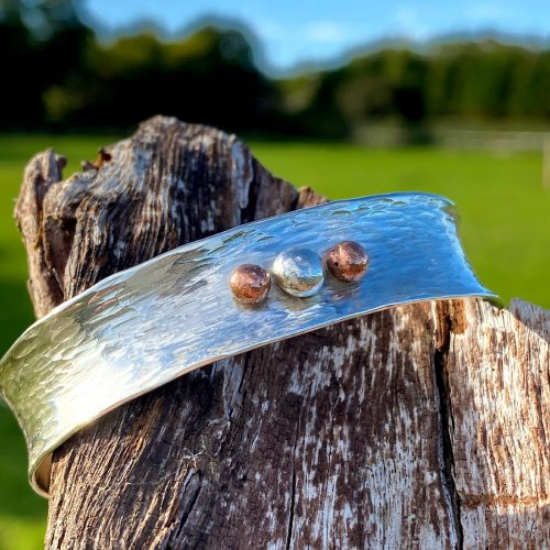handcrafted-sterling-silver-cuff-rests on a piece of driftwood
