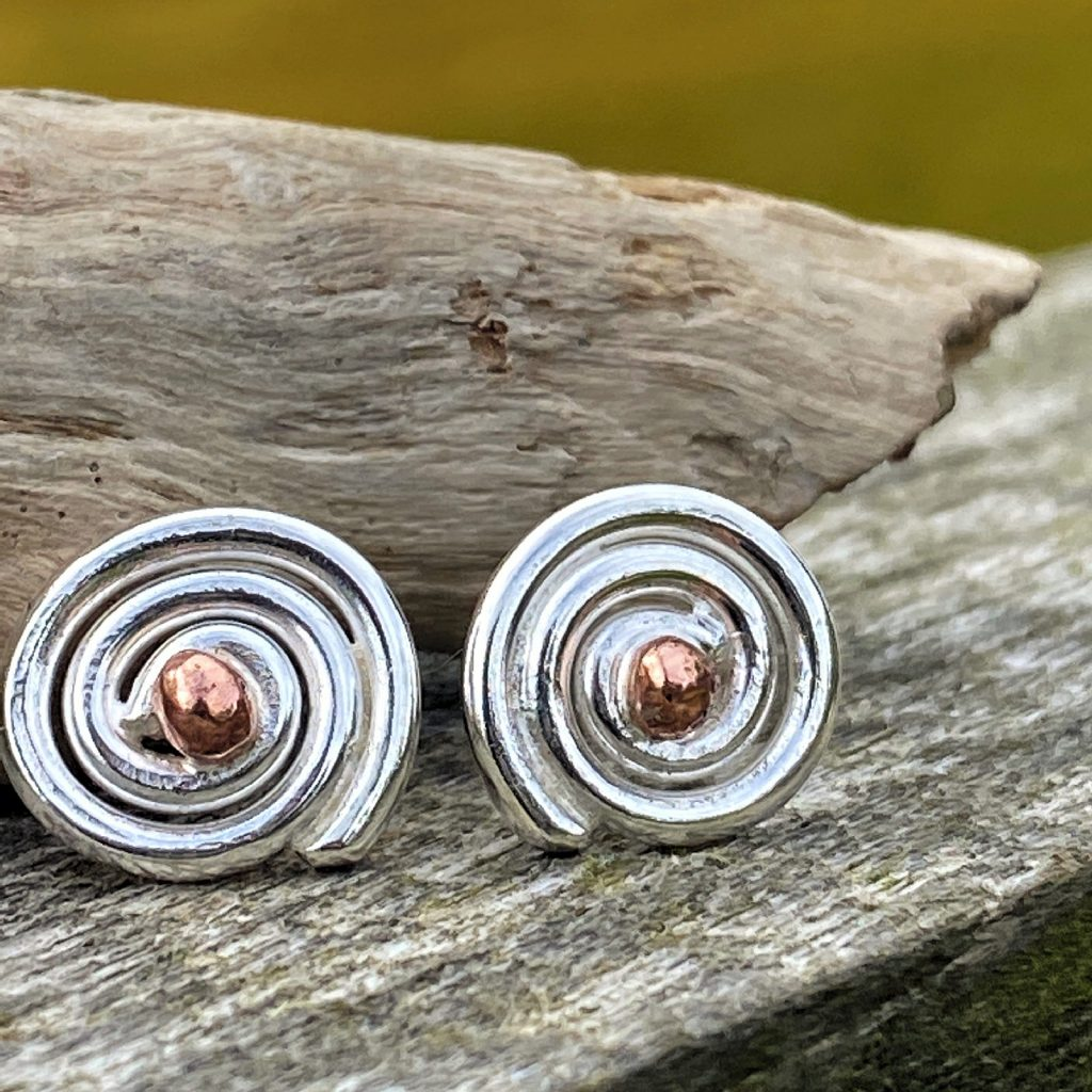 handcrafted sterling silver spiral stud earrings lying on a piece of driftwood
