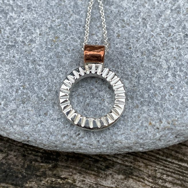 handcrafted sterling silver and copper textured circle pendant lying on a stone