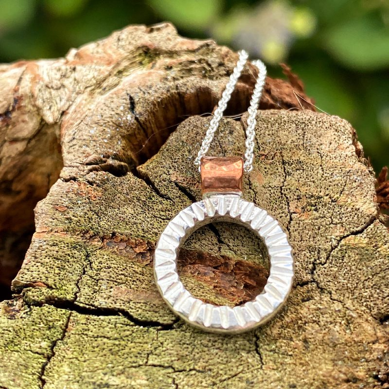 handcrafted sterling silver and copper textured circle pendant lying on a piece of driftwood