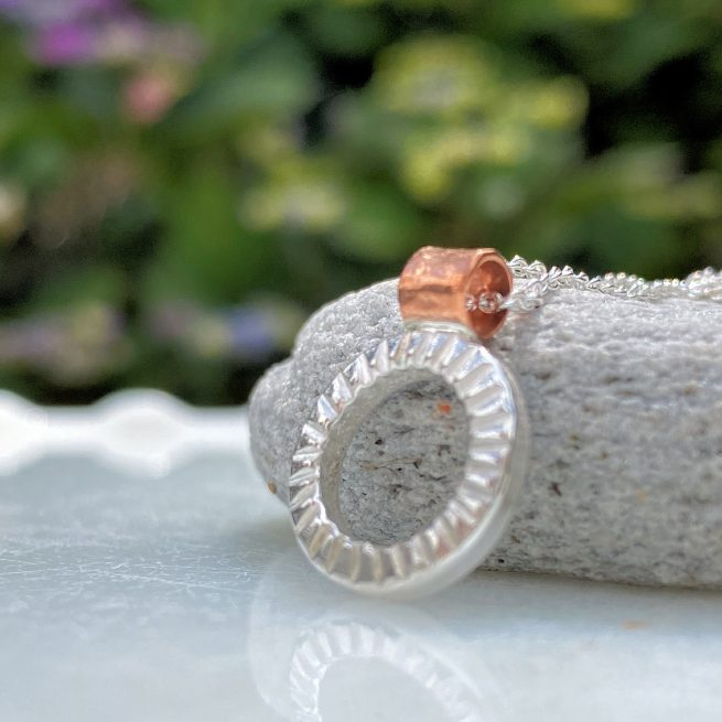 hand crafted sterling silver and copper textured circle pendant reflected on marble