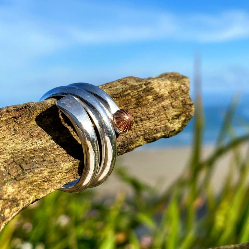 sterling silver and copper sea flower wrap ring rests on a piece of driftwood at the beach