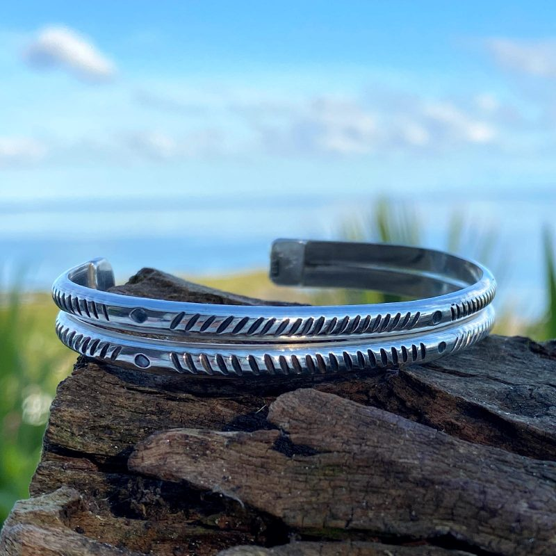 handcrafted sterling silver cuff bracelet rests on a piece of driftwood at the beach