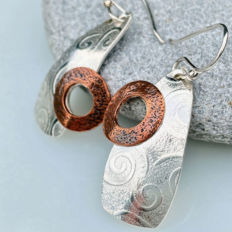 handcrafted sterling silver and copper etched beacon earrings rest on a stone