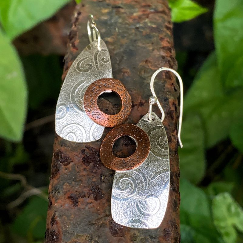 handcrafted sterling silver and copper textured beacon earrings on a piece of rusted metal