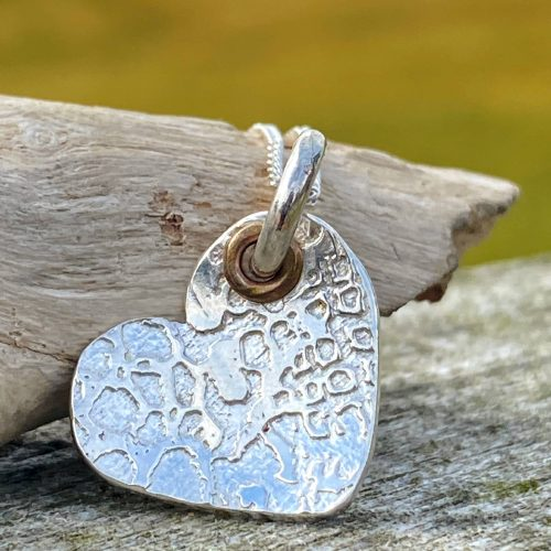 handcrafted sterling silver etched heart pendant rests on a piece of driftwood