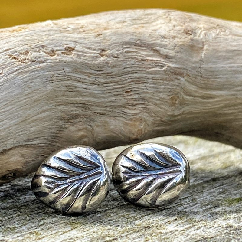 sterling silver nuggets imprinted with a leaf rest on driftwood