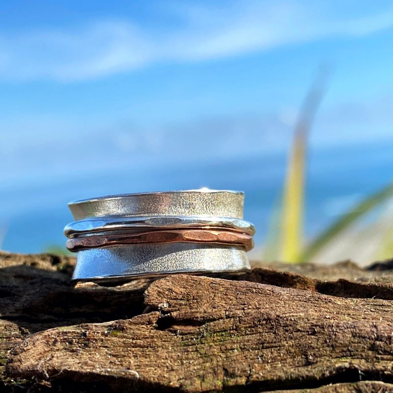 handcrafted sterling silver and copper spinner ring with two spinners on driftwood