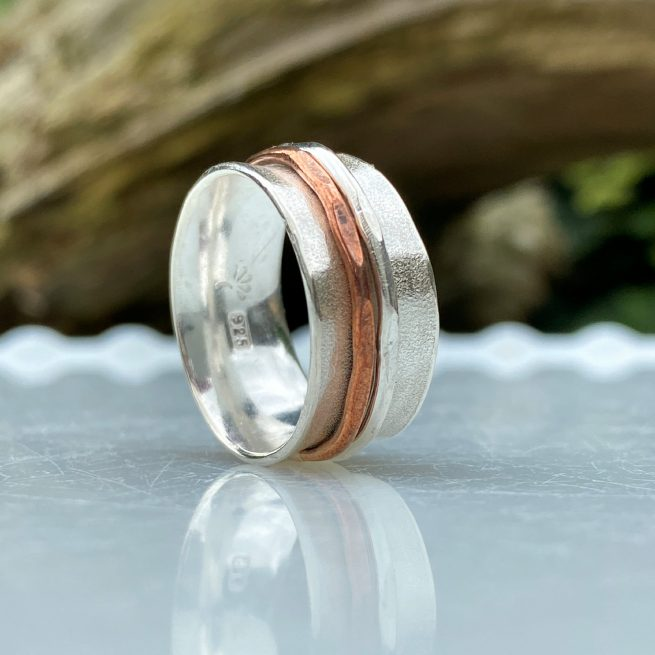 close up of handcrafted sterling spinner ring with 2 spinners