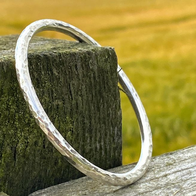 handcrafted sterling silver textured bangle rests on a fencepost