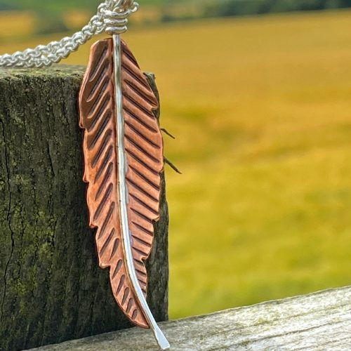handcrafted copper and sterling silver feather pendant rests on a fence post