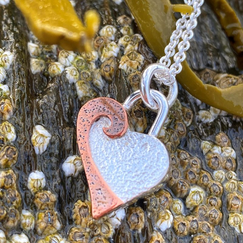 handforged sterling silver and copper heart pendant necklace on a bed of barnacles