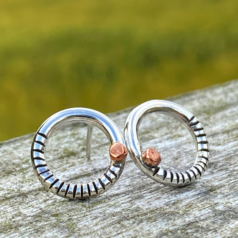 handcrafted sterling silver and copper textured circle stud earrings on drifwood