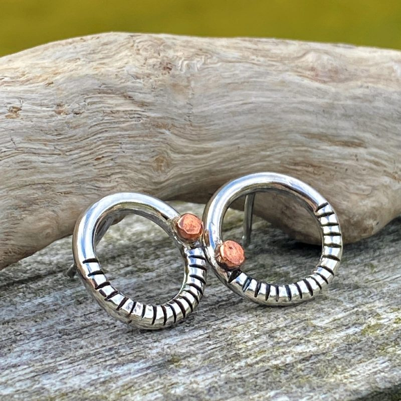 handcrafted sterling silver and copper textured circle stud earrings on driftwood
