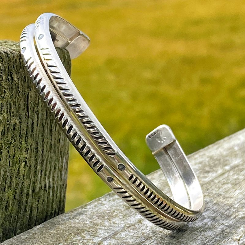 handforged sterling silver cuff bracelet on a fence post