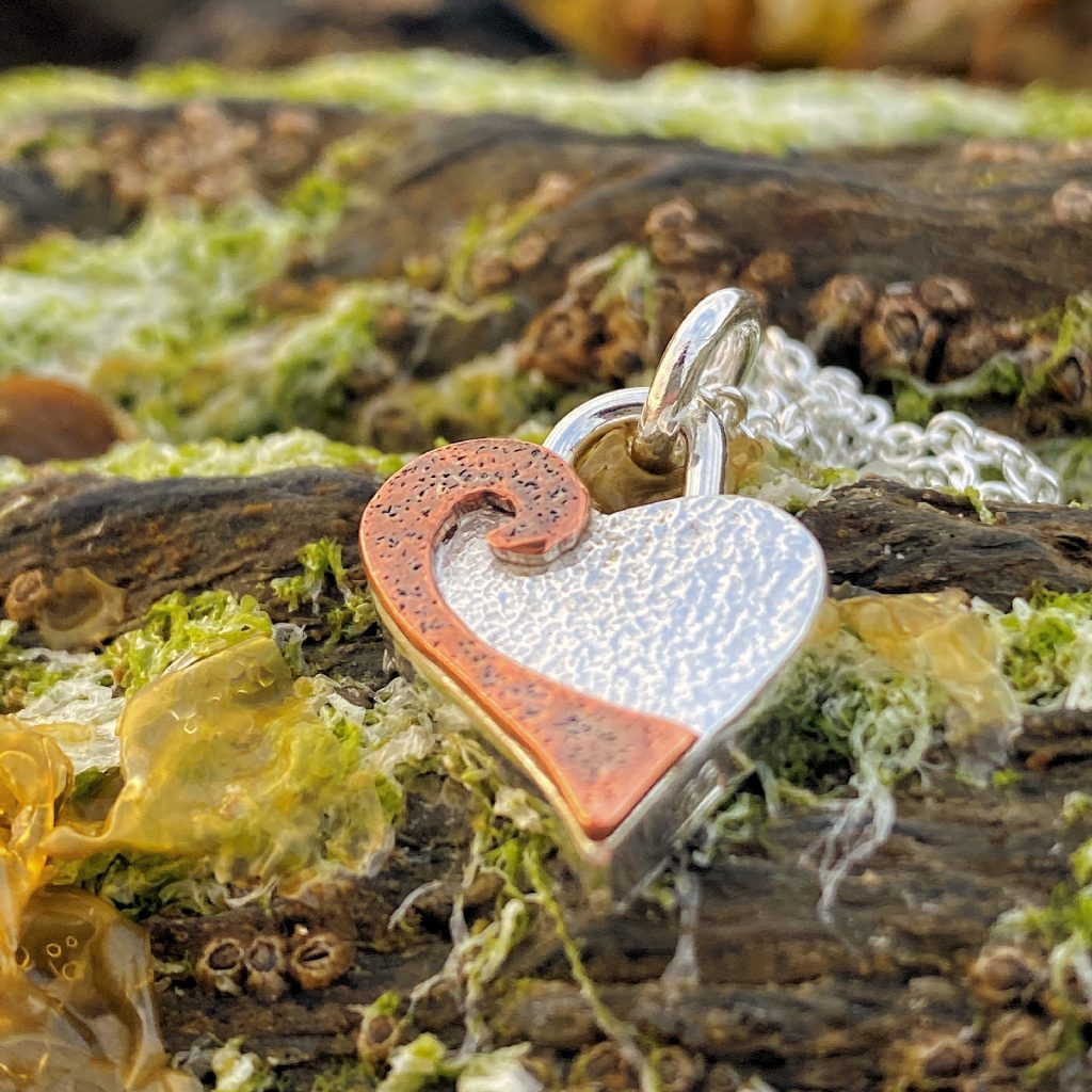 handforged sterling silver and copper heart pendant on a bed of barnacles