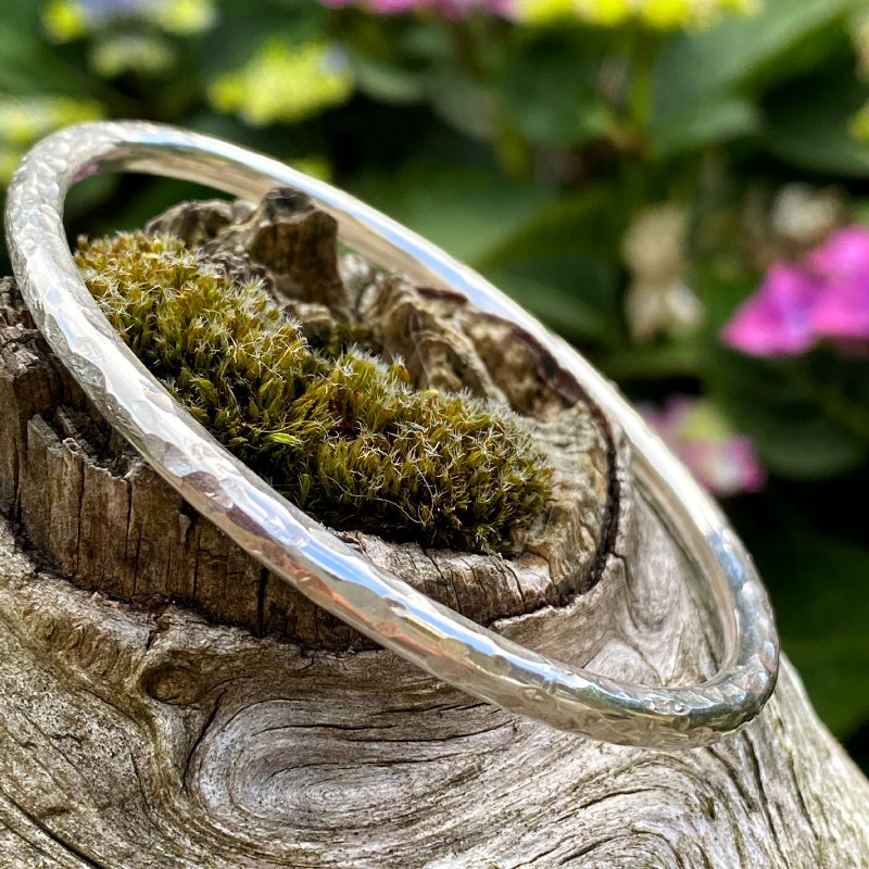 hand forged sterling silver textured bangle bracelet rests on a piece of driftwood