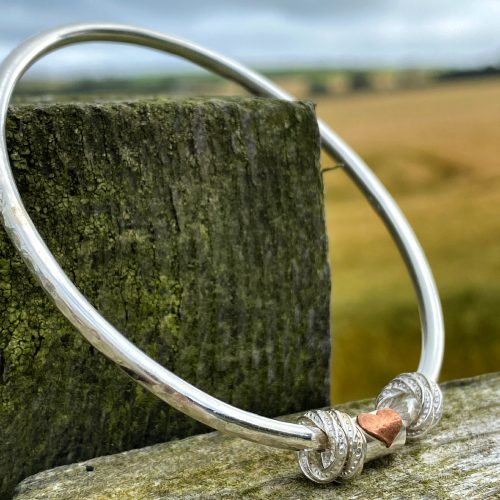 handmade sterling silver bangle bracelet with copper heart rests on a fencepost