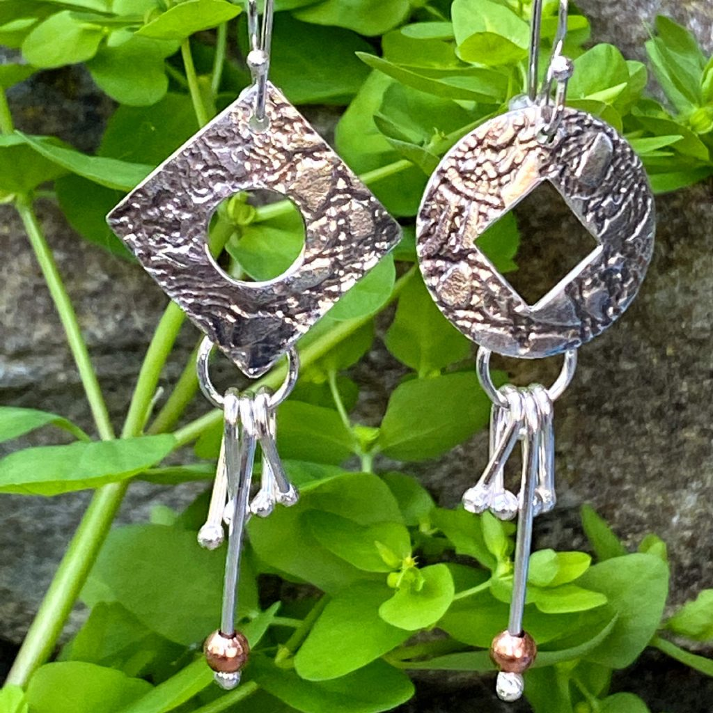 handmade sterling silver circle and square dangling earrings on leafy backdrop