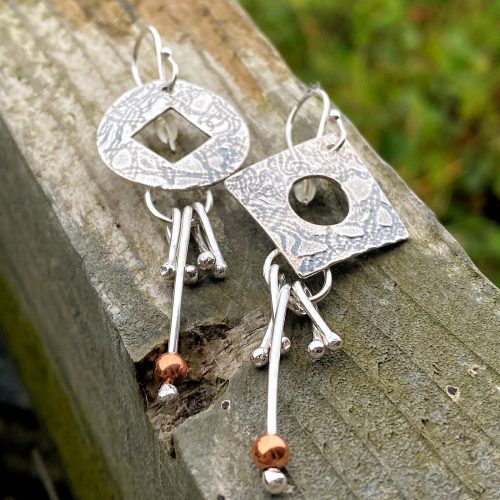 handcrafted sterling silver and copper circle and square mismatched earrings laying on a wooden fence