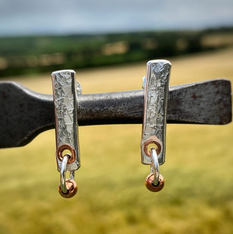 handmade sterling silver and copper fencepost earrings rest on a tool