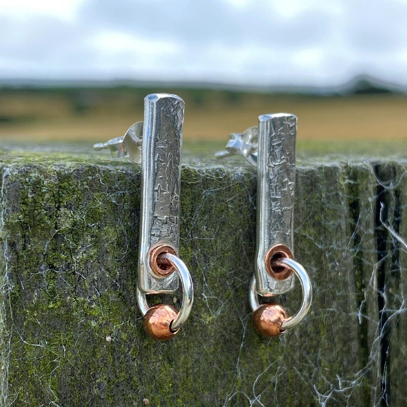 handmade sterling silver copper fencepost earrings rest on a fencepost