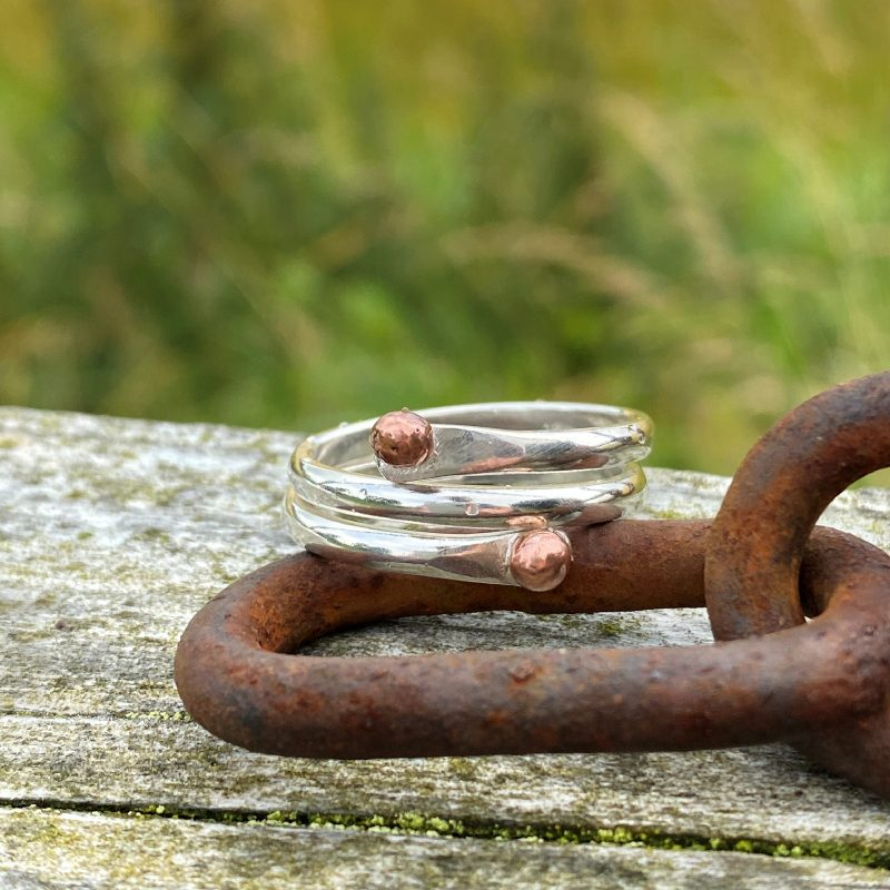handmade sterling silver and copper wrap ring rests on a rusted metal link