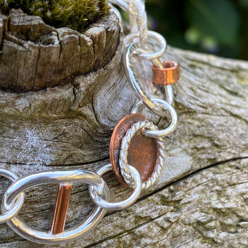 Sterling silver and copper circle dangling earrings hanging from a copper handle on wood