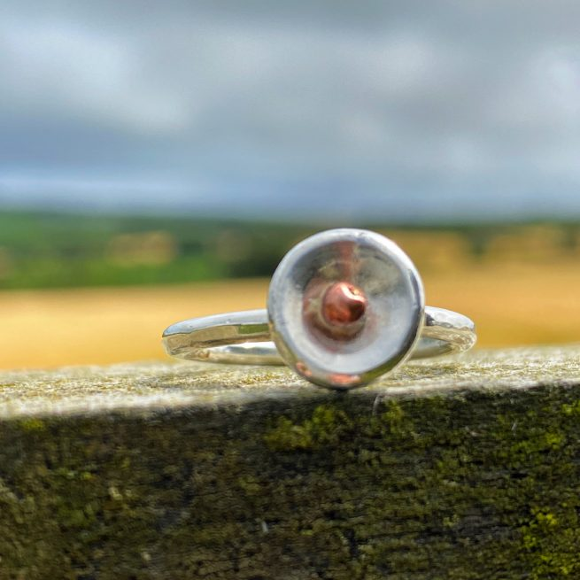 handmade sterling silver puddle ring rests on a fence post