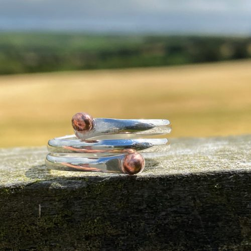 womens sterling silver copper wrap ring rests on a fence with the west cork coast behind