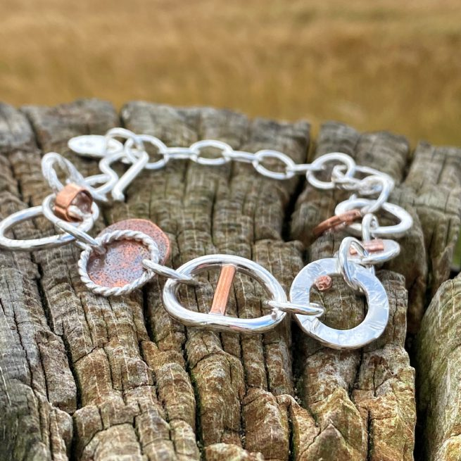 handcrafted sterling silver and copper large link chaos bracelet on wood
