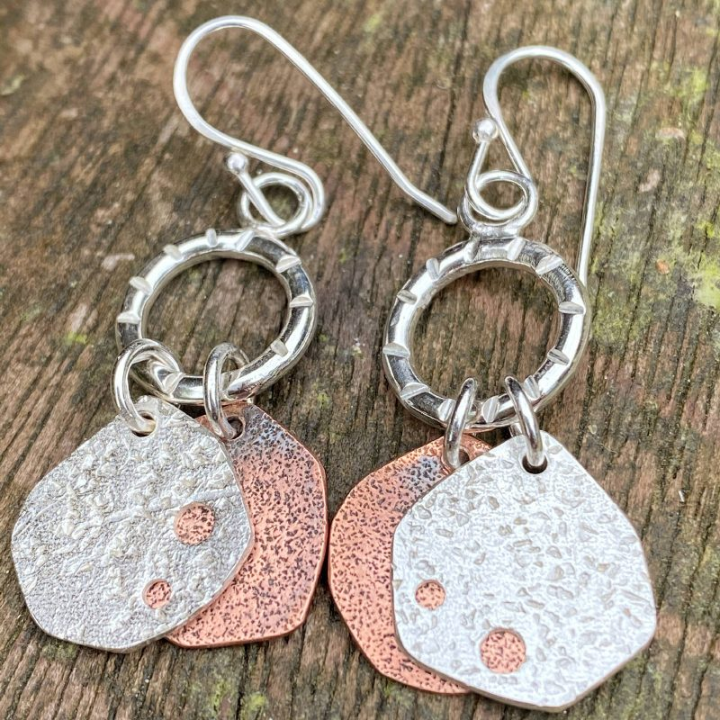 handcrafted sterling silver and copper dangling earrings rest on wood