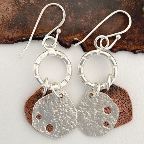 handcrafted sterling silver and copper dangling earrings on a copper back