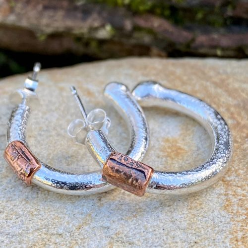 handcrafted sterling silver and copper chunky hoop earrings on a stone