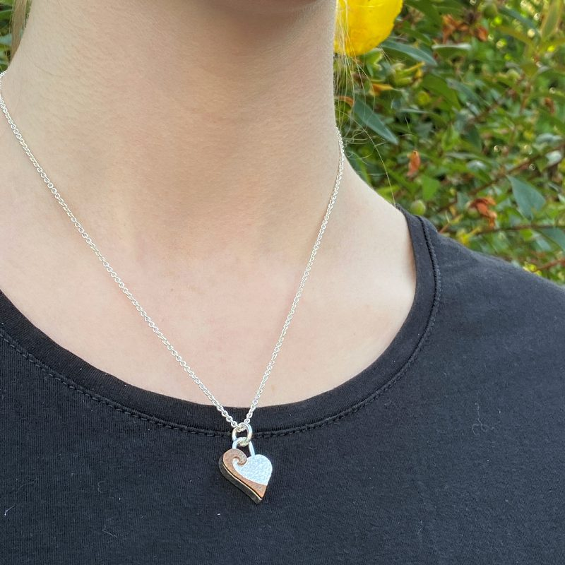 Model wearing the sterling silver and copper mighty heart pendant