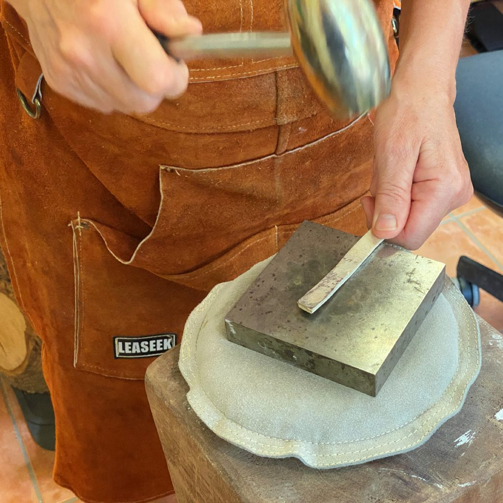 an artisan hammering sterling silver