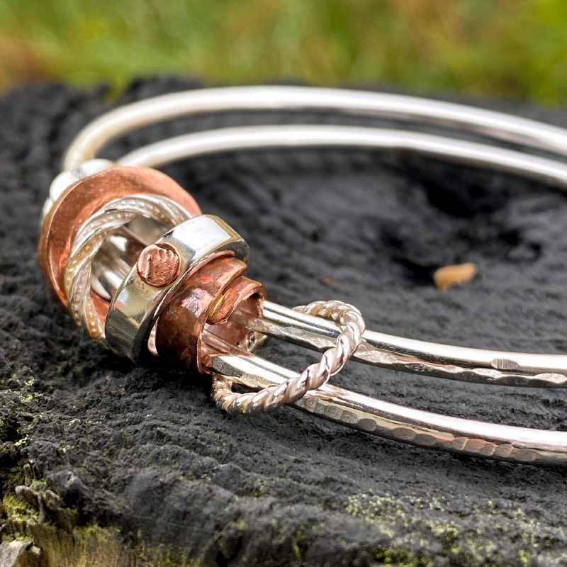 closeup of the handcrafted sterling silver and copper beads on the double bangle bracelet