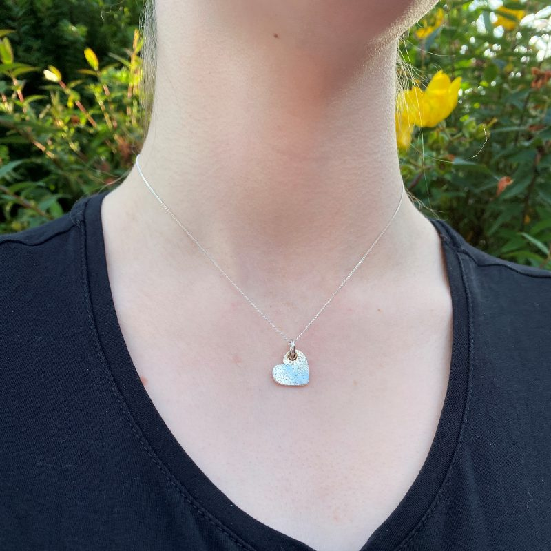 model wearing the handcrafted textured silver heart necklace