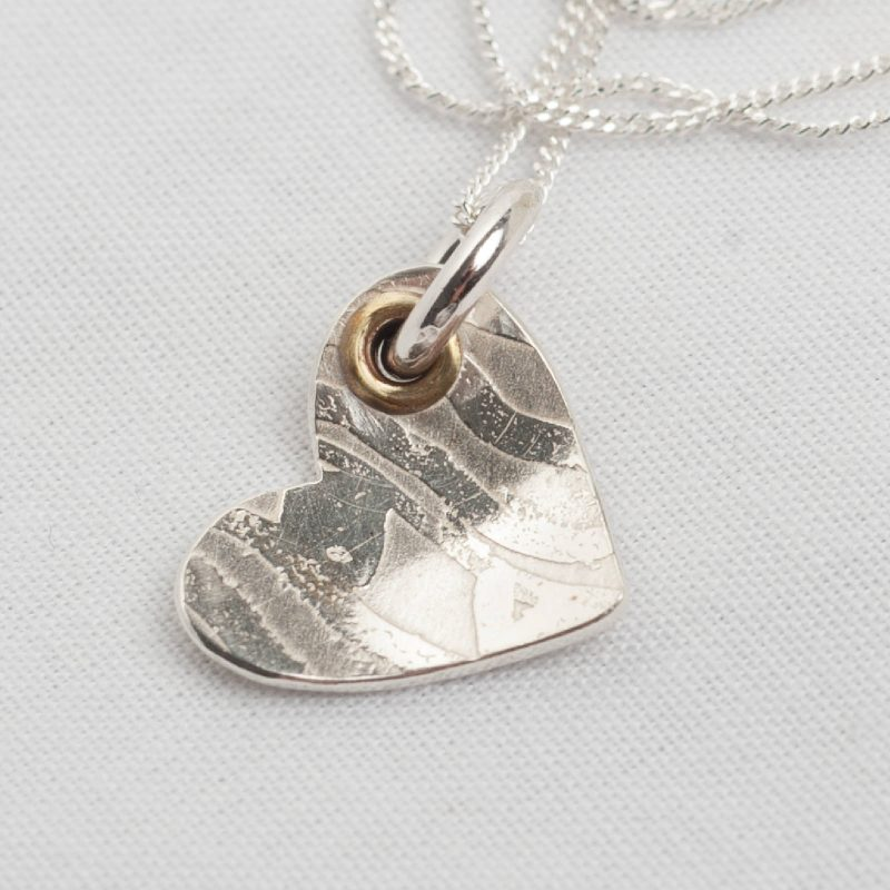 handcrafted sterling silver textured heart necklace on white background